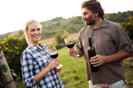 Winzer, die guten Wein im Weinberg probieren tasting