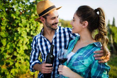 Jonge wijnboeren die wijn proeven in de wijngaard Stockfoto
