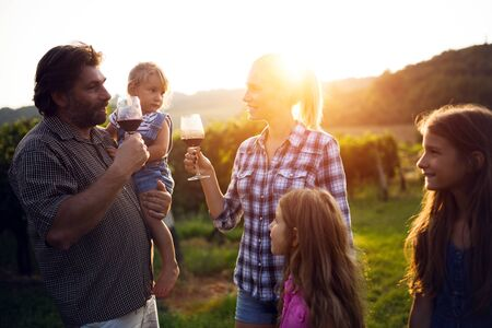 Winemaker family together in vineyard tasting vine Banco de Imagens