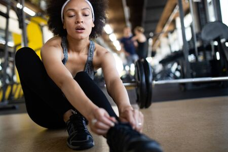 Fit african american woman exercising in fitness club