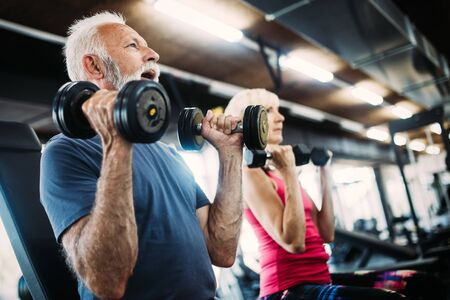 Happy senior people doing exercises in gym to stay fit Zdjęcie Seryjne