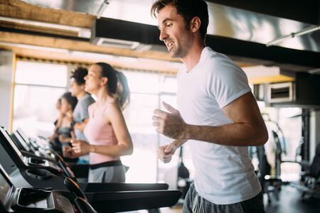 Fit people running in machine treadmill at fitness gym