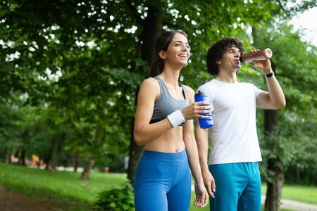 Athletic couple friend drinking water after running