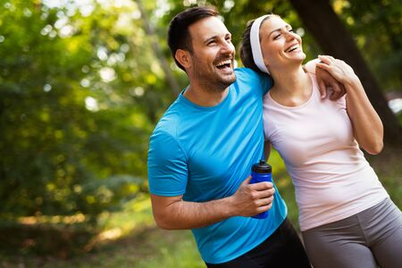 Happy couple jogging and running outdoors in nature