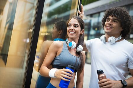 Young man and woman having break after running workout and drinking water Zdjęcie Seryjne