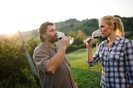Wine growers tasting nice wine in vineyard