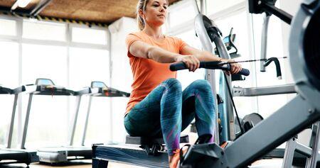 Mujer de entrenamiento entrenamiento cruzado ejercicio de cardio con máquina de remo