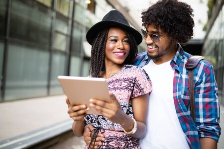 Happy young couple using a digital tablet together and smiling.
