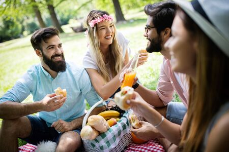 Group of friends having great time on picnic in nature Stock Photo