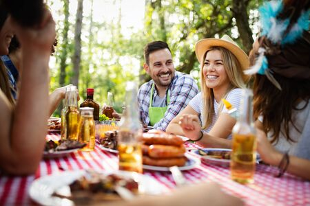 Group of happy friends eating and drinking beers at barbecue dinner Stock Photo - 129809768