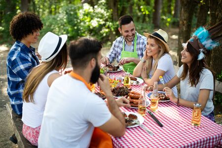 Group of happy friends eating and drinking beers at barbecue dinner Stock Photo - 129828370