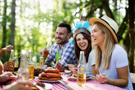 Happy friends enjoying barbecue and grill party outdoor Stock Photo - 129828371