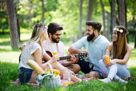 Gelukkige jonge vrienden die picknicken in het park