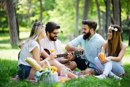 Happy young friends having picnic in the park 版權商用圖片 - 129828377