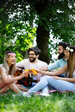 Group of friends having great time on picnic in nature Stock Photo - 129828379