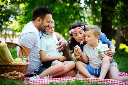 Family with children blow soap bubbles outdoors