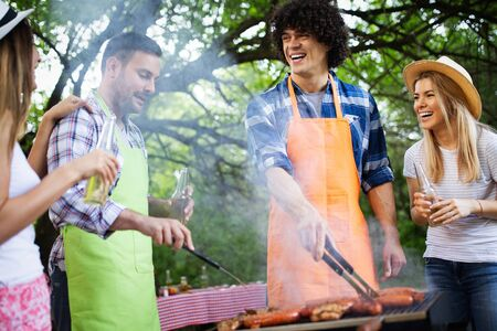 Happy friends camping and having a barbecue in nature Stock Photo - 129828455