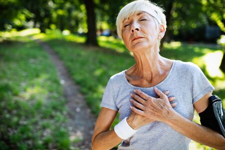 Mature woman athlete have sore left chest pain dizziness Stockfoto - 129828759