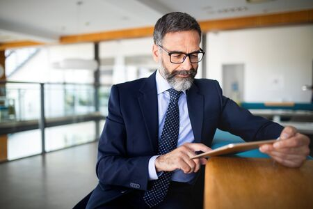 Portrait of handsome senior businessman with digital tablet in the modren office Stock fotó