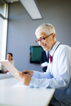 Smiling mature business woman working at modern office