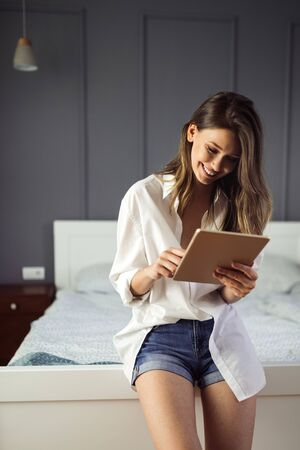 Attractive young woman using digital tablet and relaxing Banco de Imagens