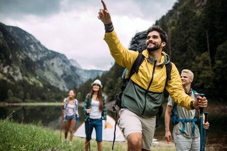 Group of happy friends with backpacks hiking together