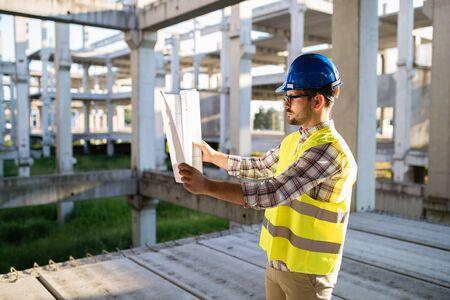 Ingenieur bezig met bouwplaats en blauwdruk te houden Stockfoto