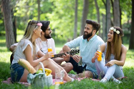 Happy friends in the park having picnic on a sunny day.