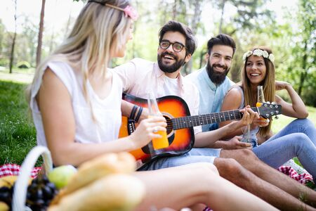 Happy group of friends relaxing and having fun on picnic in nature