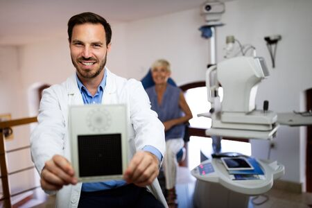 Optometrist examining mature woman in modern ophthalmology clinic