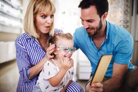 Glückliche Familie, die eine Brille im Optikgeschäft wählt