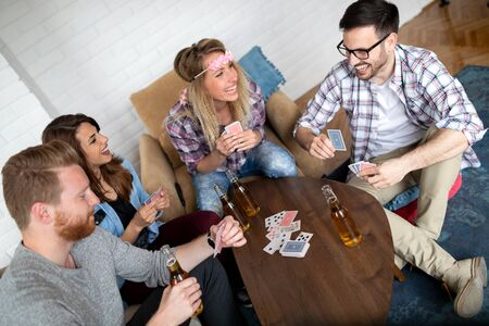 Group of friends relaxing and playing cards together. Young people hanging out together