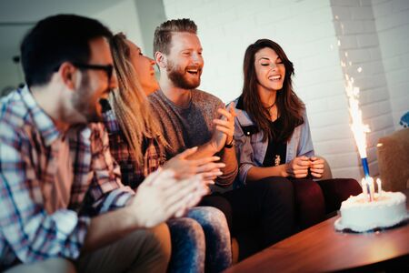 Happy group of friends celebrating a birthday party toasting the birthday girl laughing and joking Stock Photo
