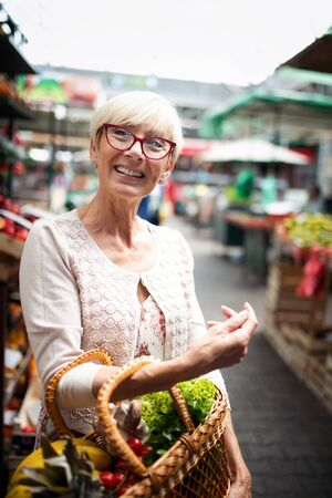 Only the best fruits and vegetables. Beautiful mature woman buying fresh food on market Stock Photo