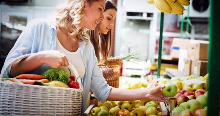 Beautiful happy women shopping vegetables and fruits Stockfoto