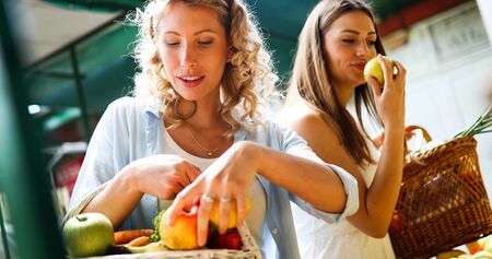 Young women shopping on the market healthy vegetables and fruits