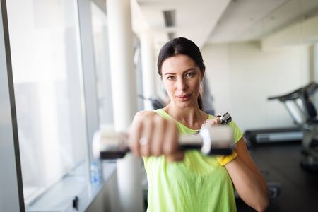 Fit woman exercising at the gym lifting weights