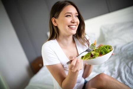 Young woman eating healthy salad after working out at home Reklamní fotografie