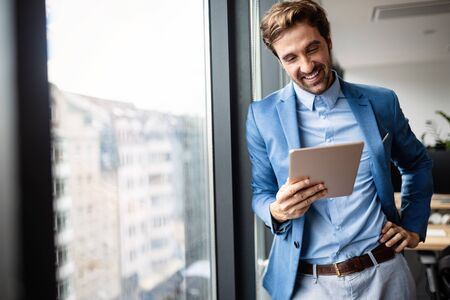 Portrait of businessman smiling while using digital tablet