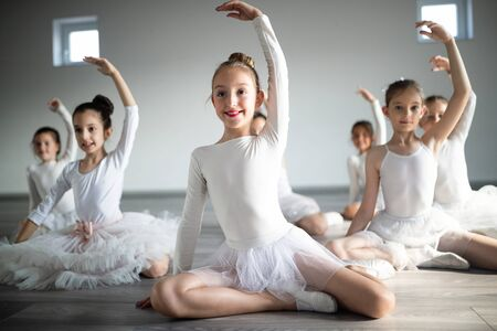 Group of fit happy children exercising ballet in studio together Stok Fotoğraf