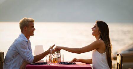 Couple sharing romantic sunset dinner on the beach Imagens