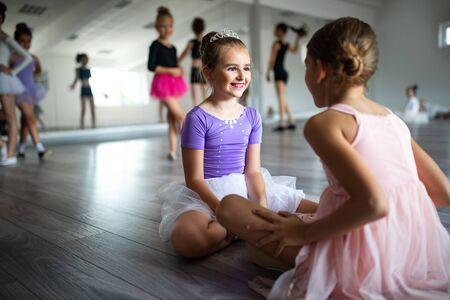 Group of little ballerinas girls doing exercises in dance school