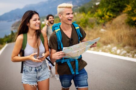 Adventure, travel, tourism and people concept - group of smiling friends with backpacks and map Imagens