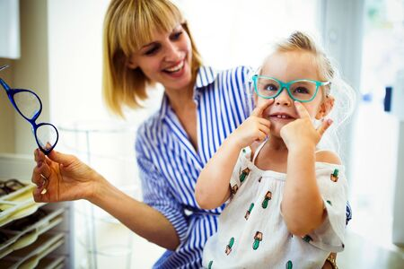 Happy mother with her cute daughter choosing glasses in optics store
