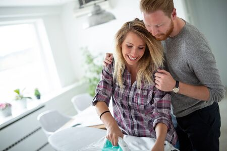Young happy couple doing the ironing together Stock Photo