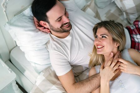 Young attractive happy couple having romantic time in bed Stockfoto