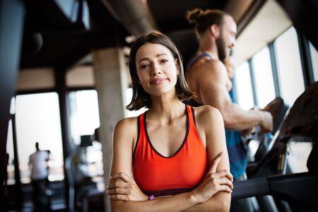 Młodzi ludzie biegający na bieżni w nowoczesnej siłowni