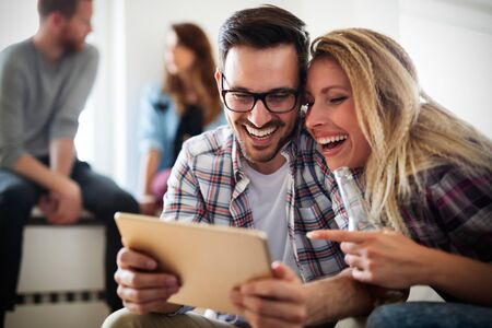 Cheerful couple using digital tablet relaxing at home