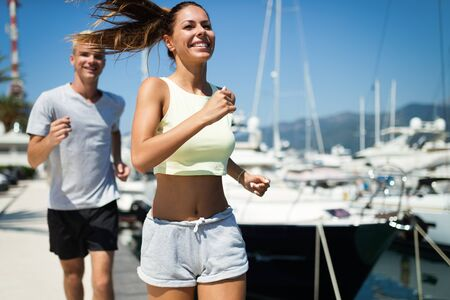 Fitness couple running training on beach. Morning cardio workout fit, sport concept