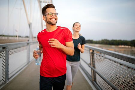 Sport couple. Young man and woman jogging outdoor Stock Photo